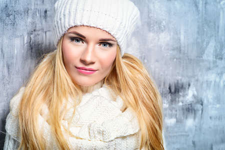 Winter beauty, cosmetics. Beautiful blonde girl wearing white winter clothes smiling at camera. Winter fashion concept. Фото со стока