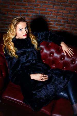 Beautiful blonde woman wearing mink fur coat posing in luxurious interior. Fashion, beauty. Winter collection. Stock Photo