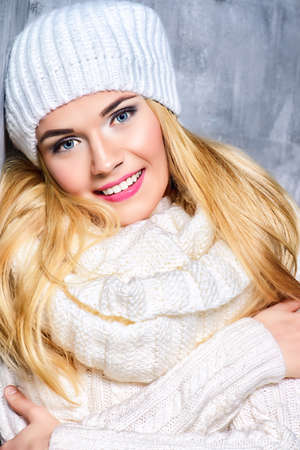 Winter beauty, cosmetics. Beautiful blonde girl wearing white winter clothes smiling at camera. Winter fashion concept. Stock Photo