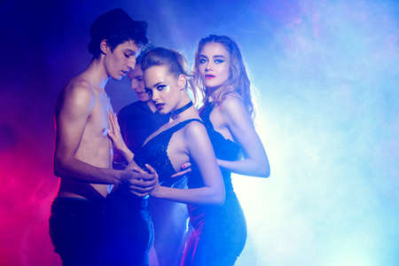 Disco, night party concept. Group of cheerful young people dancing at a night party. Beauty, fashion. Entertainment. Stock Photo