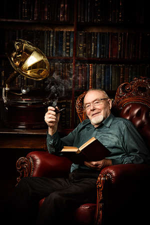 An old intelligent man listens to an old gramophone and smokes a pipe in his library. Retirement. Imagens