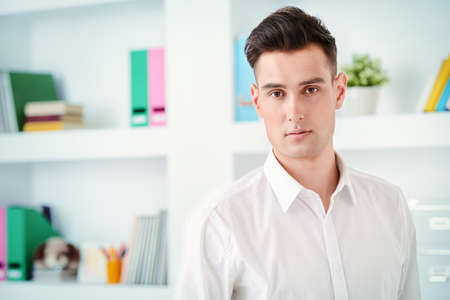 Confident young businessman in white shirt at the office. Business lifestyle. Stock Photo
