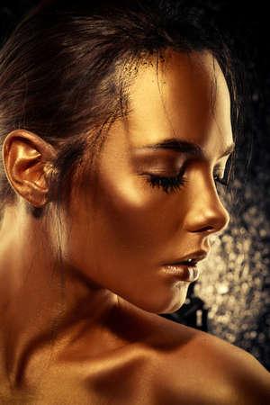 美の概念。黄金を光るとの美しい若い女性の肌のクローズ アップの肖像画。スキンケア製品、化粧品。ジュエリー コンセプト。 写真素材