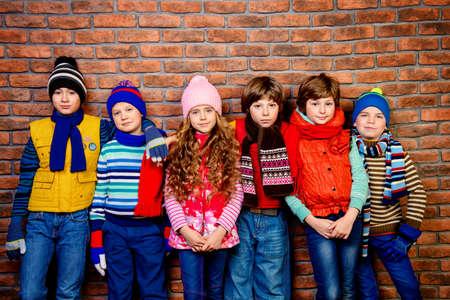 벽돌 벽에 의해 스튜디오에서 함께 포즈 행복 즐거운 어린이의 그룹입니다. 키즈 패션. 겨울옷.