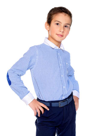 Portrait of a smiling nine year old boy in classic shirt and trousers. Kids fashion. Educational concept. Isolated over white background. Copy space.