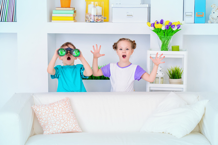 Two funny children playing together at home.