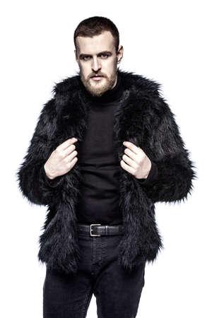 Fashion shot of a stylish bearded man wearing black fur jacket. Isolated over white. Stock Photo