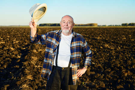 An elderly farmer standing in a plowed field.
