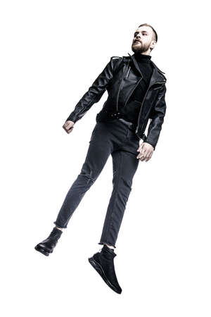 Fashion shot of a handsome brutal young man wearing black leather jacket and jeans.