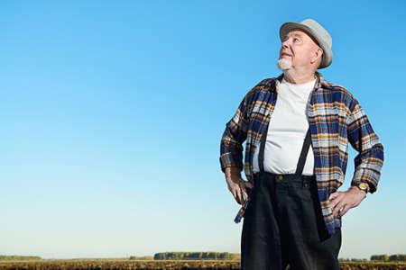 보았다고 필드에 서있는 노인 농부. 스톡 콘텐츠 - 78422145