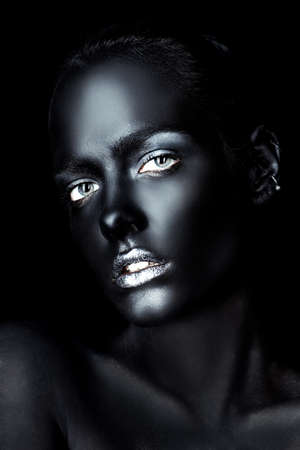 Beauty portrait. Close-up portrait of a beautiful young woman with perfect black skin and silver glitter lips. Body painting project. Cosmetics and make-up. African style.