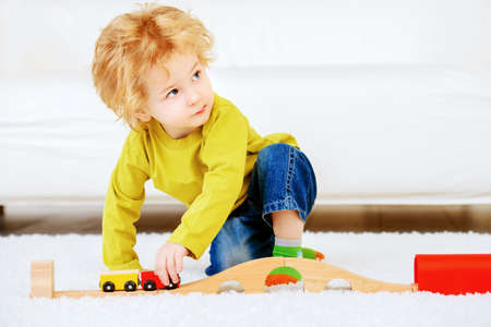 Cute 3 year old boy is playing with his toys at home. Happy childhood. Stock Photo