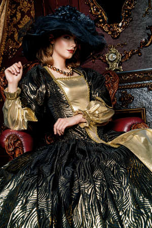 Portrait of a beautiful young woman in the lush expensive dress and elegant broad-brimmed hat in an old palace interior. Vintage style. Stock Photo