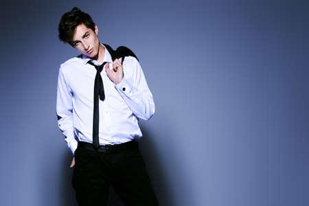 Moda girato. Bel giovane che presenta in elegante abito nero e camicia bianca. Studio shot. Archivio Fotografico - 78812267