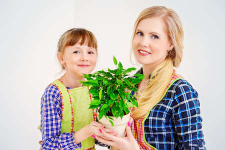 Happy loving family together. Little daughter helps her mother to take care of plants at home.