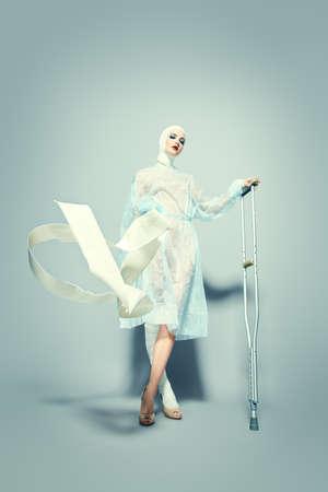 Mode schot. Prachtig vrouwelijk model in bandages en ziekenhuisjurk poseren in de studio met krukken. Schoonheid en geneeskunde, plastische chirurgie. Stockfoto
