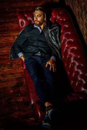 Portrait of a stylish handsome man on a leather sofa. Fashion shot. Mens clothing and accessories. Stock Photo