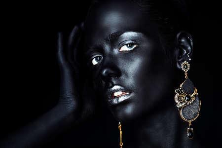Close-up portrait d'une jeune femme magnifique avec une peau noire parfaite et des lèvres de paillettes d'argent portant de belles boucles d'oreilles. Projet de peinture corporelle. Cosmétiques et maquillage. Bijoux et bijouterie. Style africain. Banque d'images - 79057873
