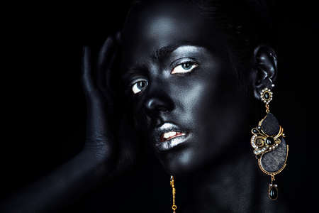 Close-up portrait of a gorgeous young woman with perfect black skin and silver glitter lips wearing beautiful earrings. Body painting project. Cosmetics and make-up. Jewelry and bijouterie. African style. 版權商用圖片