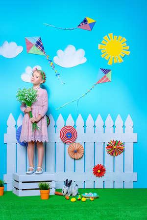Leuk gelukkig meisje staande met Paashaas in de lente decoraties. Paashaas en geschilderde eieren. Kid's mode.
