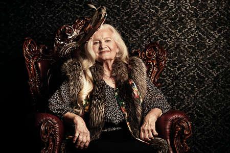 Mujer mayor de moda con el pelo rubio hermoso y el sombrero elegante que presentan en interior de la vendimia. Belleza, moda. Estilo retro. Foto de archivo - 79256882