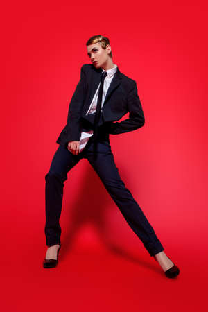 남자의 양복에서 포즈를 취하는 사치스러운 젊은 여자의 전체 길이 초상화. 남자의 스타일 의류. 빨간색 배경입니다. 패션 쐈어.