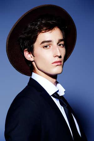 Mode schot. Portret van een knappe jongeman die zich voordeed in een elegante zwarte pak, wit overhemd en een hoed. Studio opname.