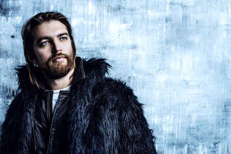 Fashion shot van een stijlvolle brutale bebaarde man het dragen van bont jas. Studio opname over grunge achtergrond. Stockfoto