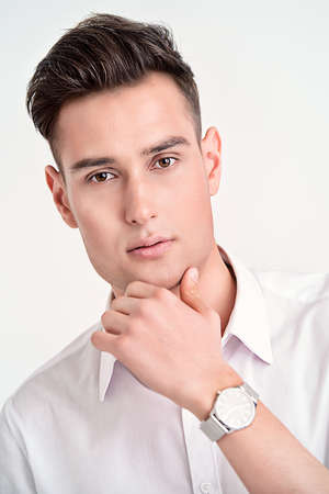 Portrait of a handsome young man in white shirt wearing a wristwatch. Mens beauty, fashion. Businessman. Copy space. Stock Photo
