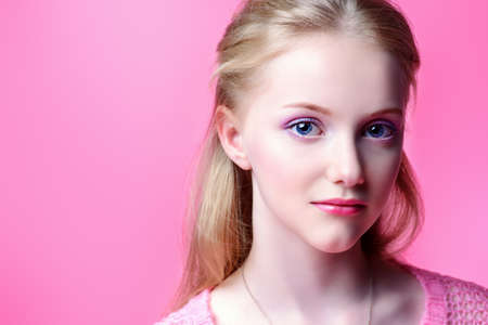 Cute girl teenager over pink background. Studio shot. Teens fashion.