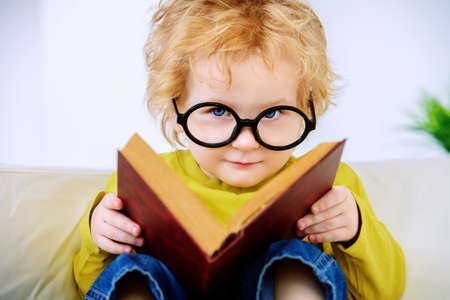 Small three year old boy in glasses is reading fairy tales. Educational concept. Stock Photo