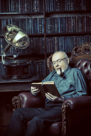 An old intelligent man listens to an old gramophone in his library.
