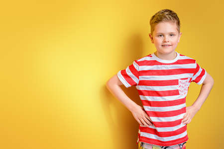 Portrait of a cute boy over bright yellow background. Clothes for children. Kids fashion.