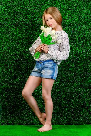 Mooie zomermeisje staande met een boeket tulpen in een groene zomertuin. Kindermode.