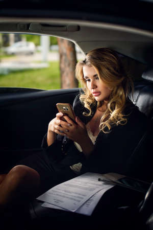 Portrait of a beautiful business woman with her cell phone in a car.