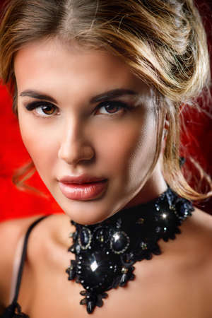 Charming young woman with evening make-up and hairstyle over red background. Jewellery, earrings and necklace. Beauty and fashion concept.