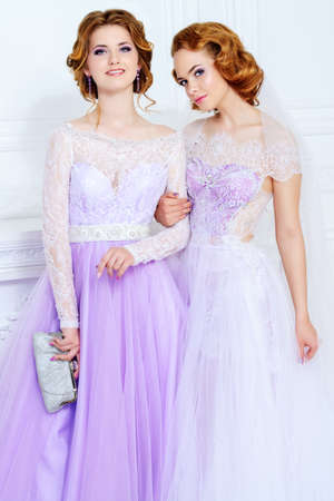Charming bride and bridesmaid stand together in beautiful dresses and laugh. Wedding fashion. Stock Photo