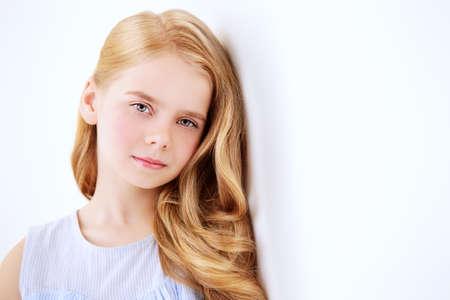 Mooi meisje in een lichtblauwe jurk die zich in een witte kamer vol licht bevindt. Kid's mode. Kapsel. Stockfoto
