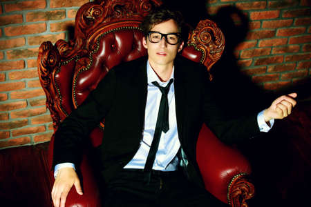 Glamorous sexy young man in elegant black suit and glasses sitting in vintage armchair. Male beauty, fashion. Stok Fotoğraf