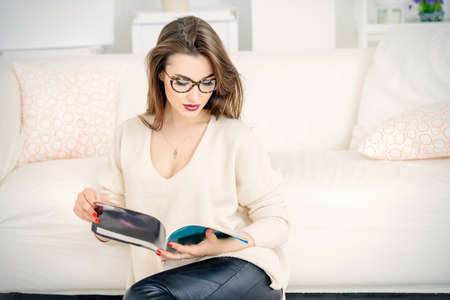 家で雑誌を読んで美しい女性の肖像画。美容、ファッション。光学系のスタイルです。