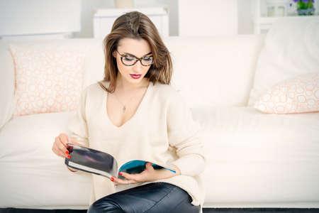 Portrait of a beautiful  woman reading a magazine at home. Beauty, fashion. Optics style.