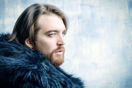 모피 코트를 입고 세련 된 잔인 수염 난된 남자의 패션 쐈어. 그런 지 배경 위에 촬영 스튜디오입니다. 스톡 콘텐츠 - 80050619