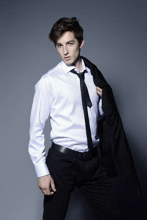 Fashion shot. Handsome young man posing in elegant black suit and white shirt. Studio shot. Stock Photo - 80050450