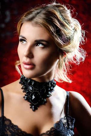 夕方化粧と髪型赤い背景の上の魅力的な若い女性。ジュエリー、イヤリング、ネックレス。美しさとファッションのコンセプトです。