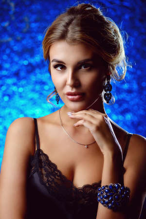 Beautiful young woman with evening make-up and hairstyle. Jewellery, earrings. Beauty and fashion concept.