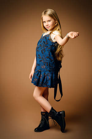 Childrens fashion. Cute eight year old girl with long blonde hair posing in summer dress and a bag. Studio shot. Full length portrait. Stock Photo