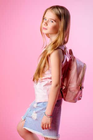 Kindermode. Leuk acht jaar oud meisje met een zomerjurkkleding en een tas die op roze achtergrond uitstelt. Studio shot.