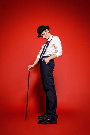 Fashion shot. Attractive young model posing in a mans suit and bowler hat. Mans style clothing. Red background.