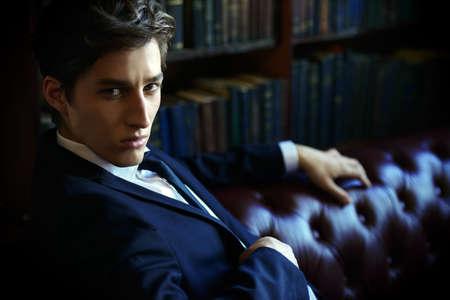 Bel giovane vestito dai libri in una stanza con interni classici. Stile di affari. Archivio Fotografico - 80229423
