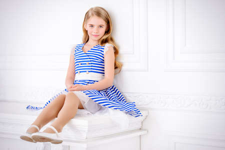 Cute little girl in a beautiful summer dress posing in a room with classical white interior. Kids fashion. Stok Fotoğraf